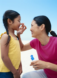 A woman applies sunscreen to a child